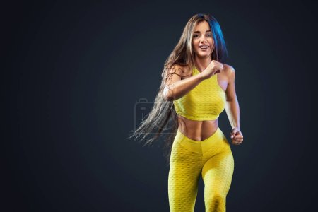 Strong athletic, woman sprinter, running on black background wearing in the yellow sportswear, fitness and sport motivation. Runner concept with copy space.