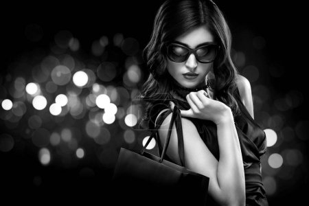 Photo for Beautiful young woman make shopping in black friday holiday. Girl with black bag on dark background. - Royalty Free Image