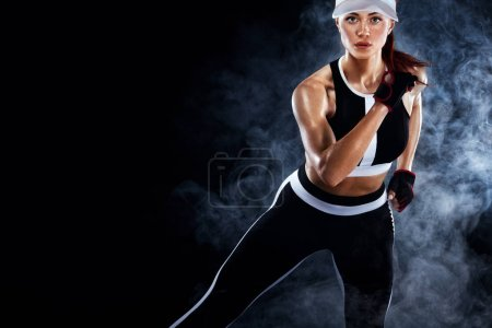 Photo for A Strong athletic, female runner on the black bacground wearing a tight, fitness outfit. - Royalty Free Image