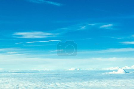 Photo for Airplane flying in the blue sky among clouds and sunlight. - Royalty Free Image