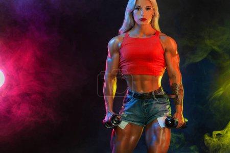 Photo pour Femme en forme sportive, athlète avec haltères rend l'exercice de fitness sur fond noir avec des lumières . - image libre de droit