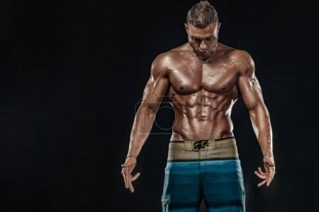 Photo for Young strong man bodybuilder on background with lights. - Royalty Free Image