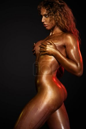 Topless sporty woman in dancer and athlete with gold body art posing on black background with colorful lights. Wellness category.