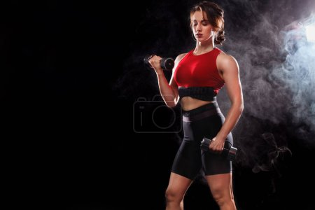 Photo for Sporty and fit woman doing exercising at black background to stay fit. - Royalty Free Image