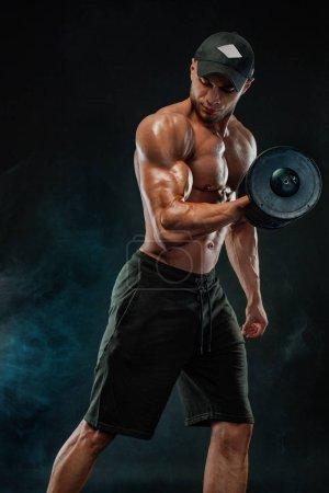 Photo pour Jeune sportif sans chemise athlétique - modèle de fitness avec haltère dans la salle de gym. - image libre de droit