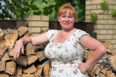 Photo pour Portrait d'une femme rurale rousse près d'une pile de bois - image libre de droit