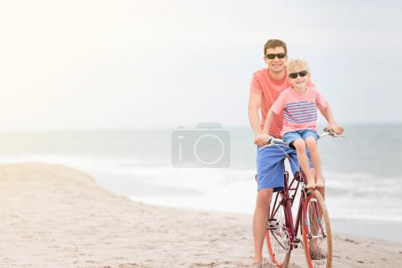 Photo for Family of two, father and son, enjoying casual bike ride at the beach, active vacation concept - Royalty Free Image