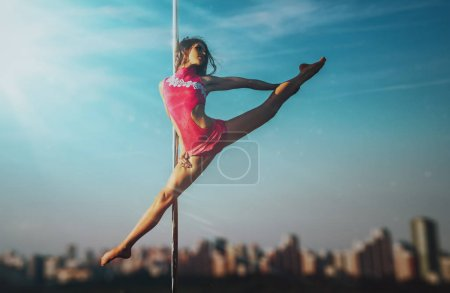 Young slim woman pole dancing on sky and city background