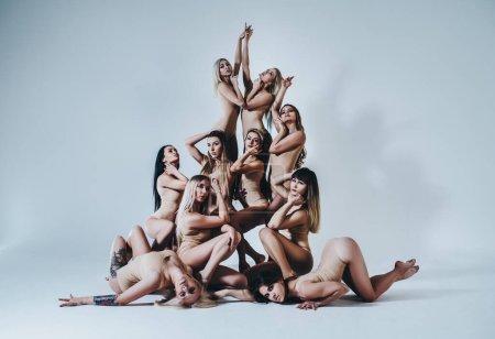 Photo pour Grande équipe de femmes de fitness et de danse posant sur fond de mur blanc - image libre de droit