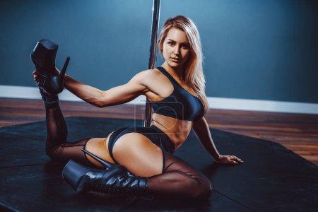 Photo pour Jeune femme blonde sexy pole dance - image libre de droit