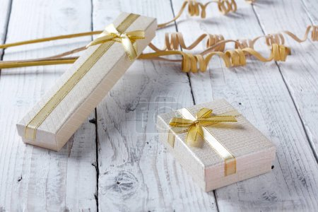 Golden gift boxes with a bow on old vintage wooden table