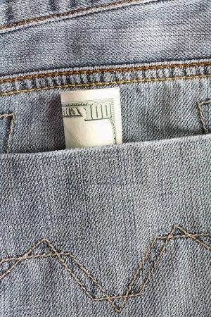 Hundred dollar bills sticking in the back pocket of denim blue jeans