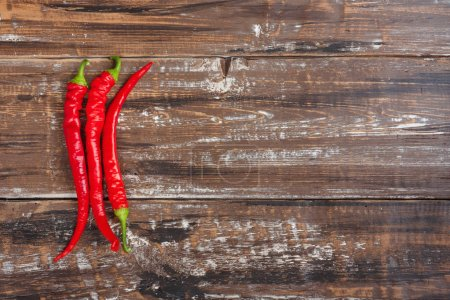 The composition of chili red hot peppers on wooden table. Top view flat lay group objects