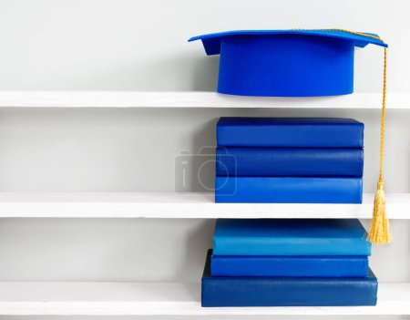 Photo for Graduation blue mortarboard on top of stack of books on wooden shelf on background of vintage wall - Royalty Free Image