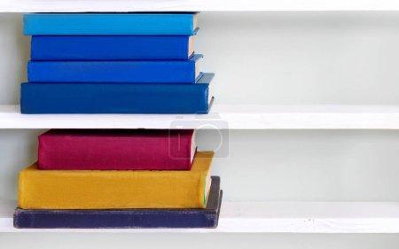 Photo pour Empilement de vieux livres bleus vintage sur étagère en bois dans la bibliothèque universitaire pour la lecture - image libre de droit