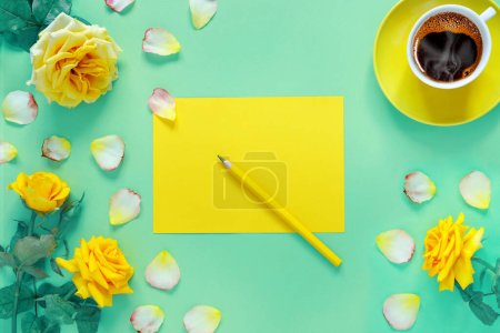 Photo for Bouquet of beautiful yellow roses and cup of hot fresh aromatic coffee on  green paper background. Notebook sheet  and  pencil for your text - Royalty Free Image