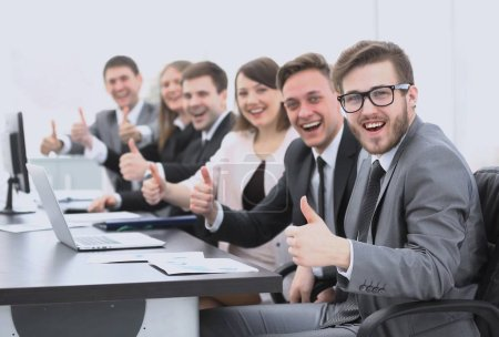 business team with thumbs up while sitting at his Desk