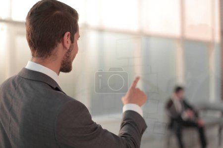 rear view.businessman pointing his finger at the office window