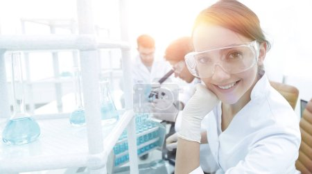 Investigator checking test tubes, Woman wears protective goggles