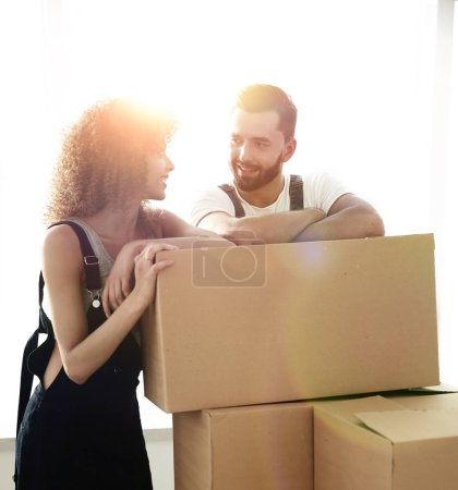 Photo for Happy couple honeymooners standing near boxes in their new apartment. - Royalty Free Image