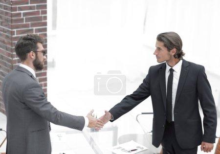 Foto de Apretón de manos de los socios comerciales en una oficina brillante - Imagen libre de derechos