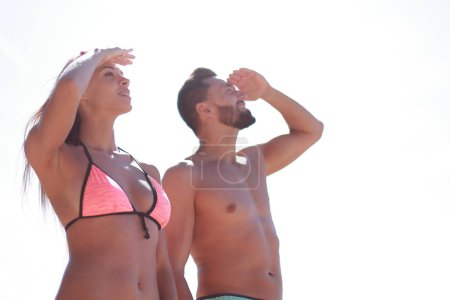 Young couple in swimsuits looking at the sea,