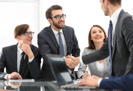 Photo pour Partenaires commerciaux poignée de main sur les objets d'affaires sur le lieu de travail. - image libre de droit