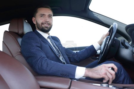 Photo for Confident businessman sits at the wheel of a car and looks at the camera - Royalty Free Image