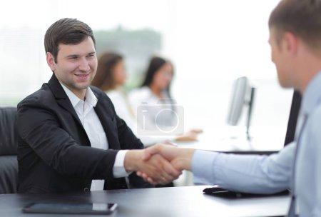 Photo pour Poignée de main partenaires d'affaires à votre bureau - image libre de droit