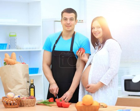 Pregnant woman and her husband standing together in the kitchen