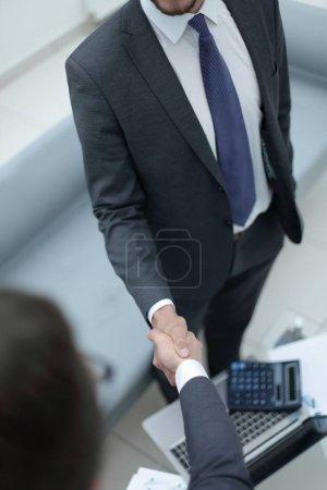close up.handshake trading partners over the desktop