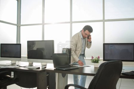 businessman working on a calculator standing in a bright office