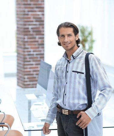 junger Mitarbeiter steht im Büro