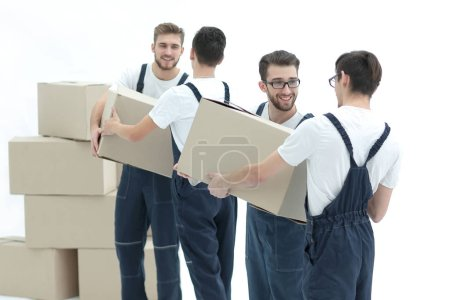 Photo workers pass each other boxes when moving flats.