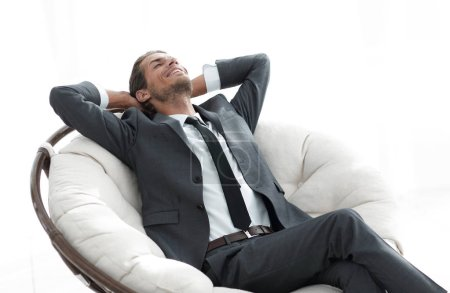 Photo pour Jeune homme d'affaires méditant dans un grand fauteuil confortable. photo avec espace de copie - image libre de droit