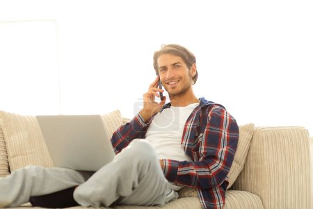 serious young man with laptop talking on mobile phone