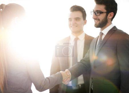 Photo pour Poignée de main aux partenaires financiers sur le fond du bureau - image libre de droit