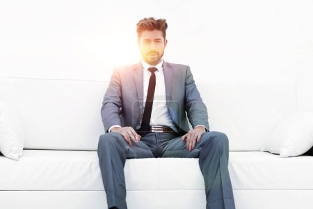 Successful businessman sitting in a suit smokes