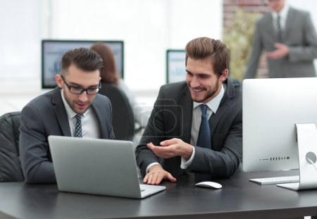 cheerful colleagues having fun sitting at desk with laptops