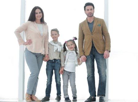 Photo pour Portrait d'une famille moderne debout près d'une grande fenêtre .photo avec espace de copie - image libre de droit