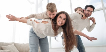 happy parents play with their children in the spacious living room