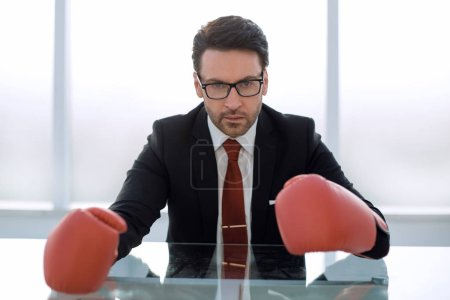 close up.responsible businessman Boxing gloves sitting at the Desk