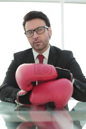close up.confident businessman Boxing gloves sitting at his Desk