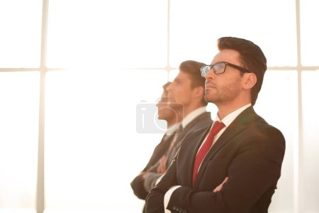 side view.a group of business partners looking at a copy space