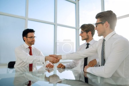 handshakes of business people over the Desk in a bright office