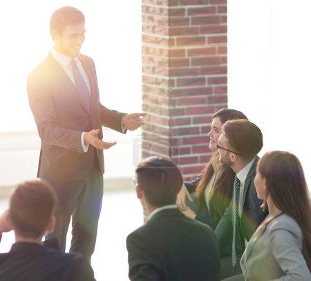 Photo pour Cinq employés souriants assis autour de leur gestionnaire - image libre de droit