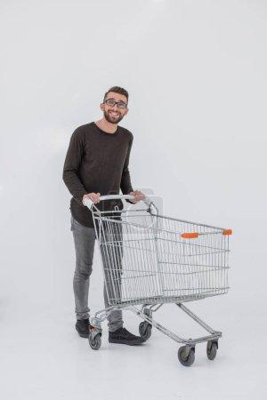 Photo pour Portrait complet d'un homme heureux courant avec un chariot isolé sur fond blanc - image libre de droit