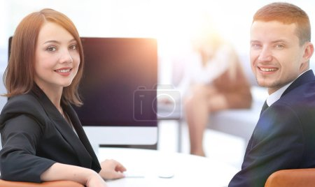 members of the business team sitting at Desk and looking at camera