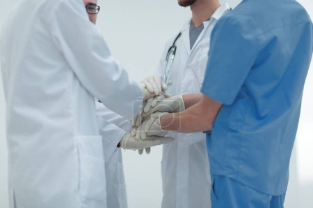Photo for Group of doctors,clasped their hands together.the concept of teamwork - Royalty Free Image