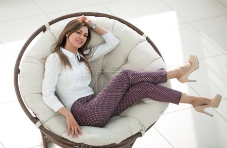 tired young woman resting in a soft round chair